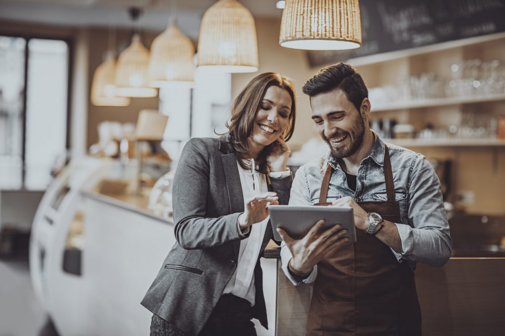 Shot of a smiling cafe owner  and employee barista standing inside a coffee shop looking at new menu on a digital tablet