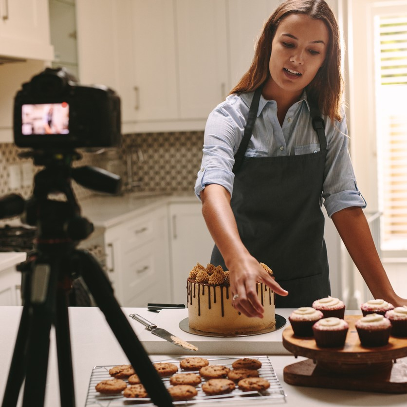 Retail Website Lifestyle Content -  Social media influencer woman recording video content in kitchen, showing confectionery on table. Female confectioner filming herself of her online culinary show.